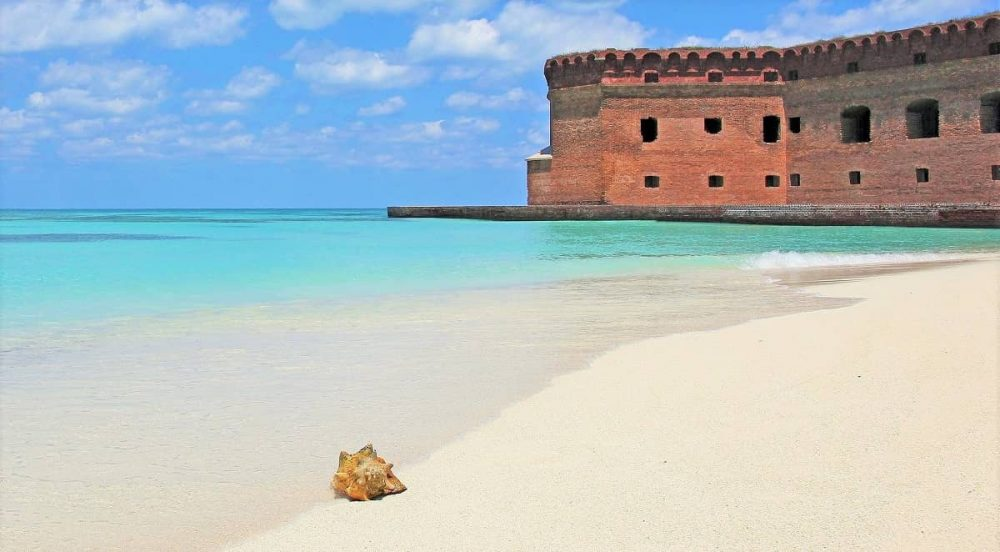 Blue water, sandy beach and red fort during daytime