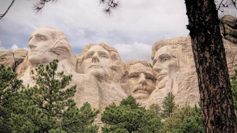 Mount Rushmore sculpture, green trees and cloudy sky