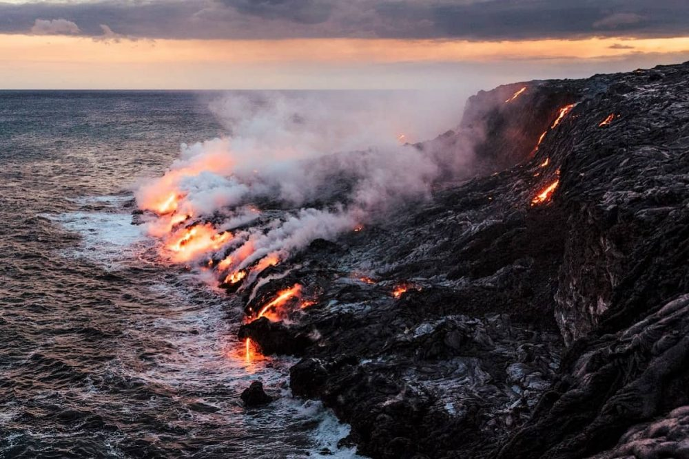 Lava flowing from rocks into the Pacific Ocean in Hawaii Volcanoes National Park