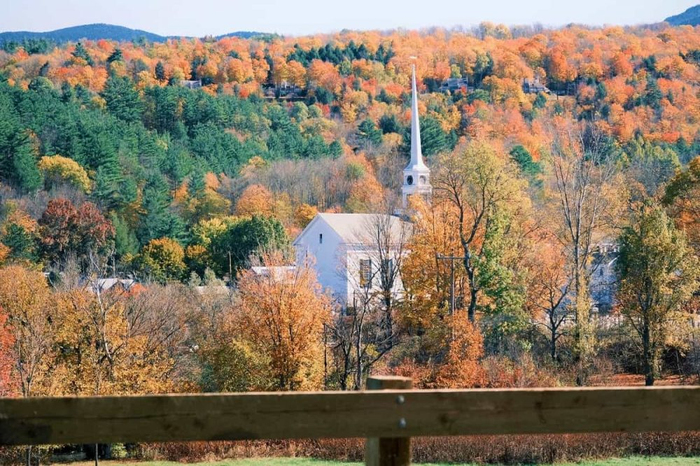 White church nestled among trees and mountains in Stowe.